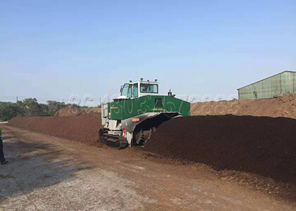 Self-propelled compost turner for organic waste processing